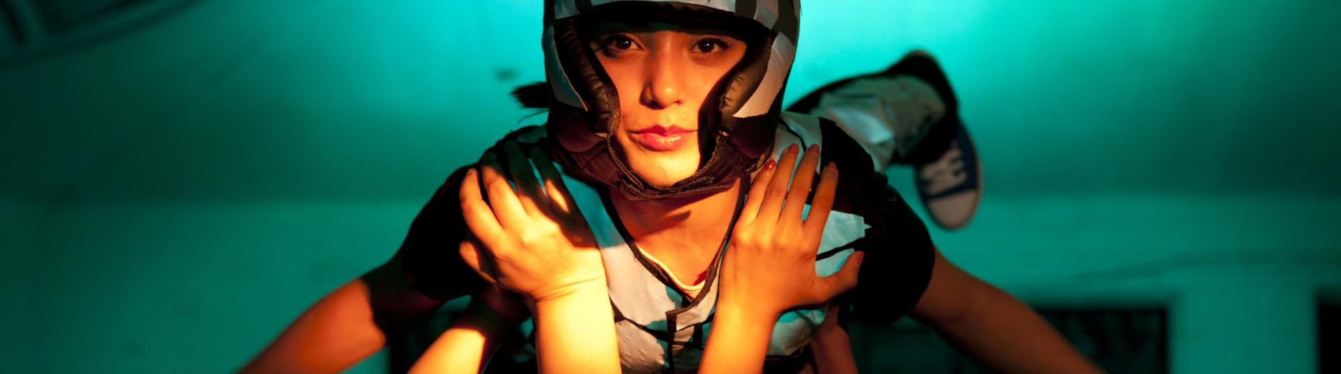A dancer in a helmet is held up by other dancers
