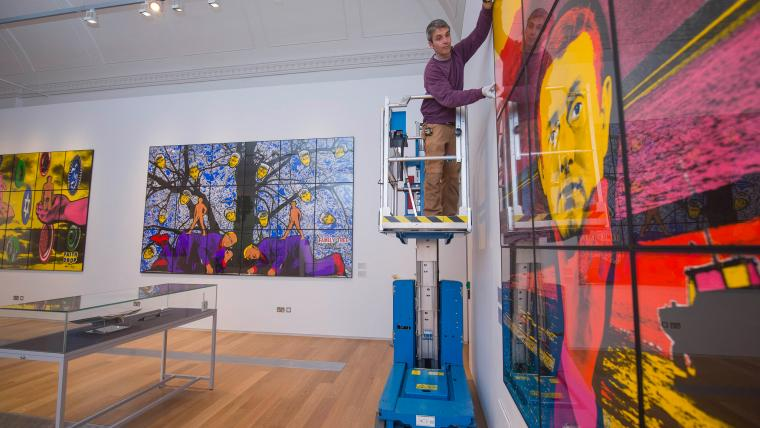 A gallery attendant hangs artwork at RAMM Exeter.