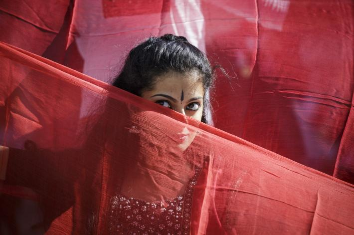 A dancer hides behind a veil of fabric.