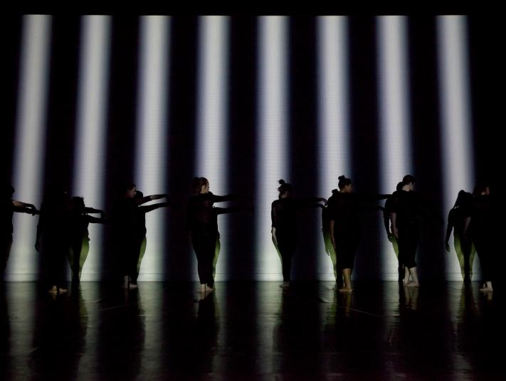 Dancers dressed in black on a black stage are illuminated by strips of white light.