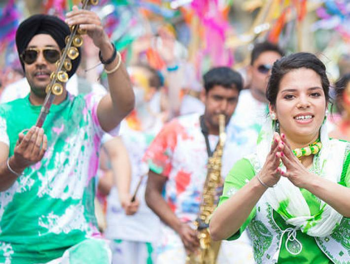 Participants at the Indian Festival dance down the street in bright coloured outfits.
