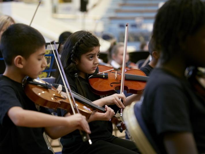 Children playing violins as part of an orchestra.