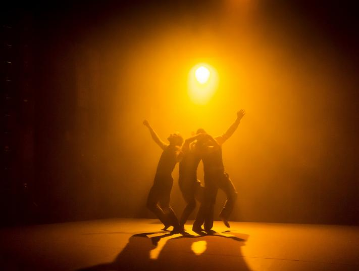 Three performers stand beneath a blazing yellow light.