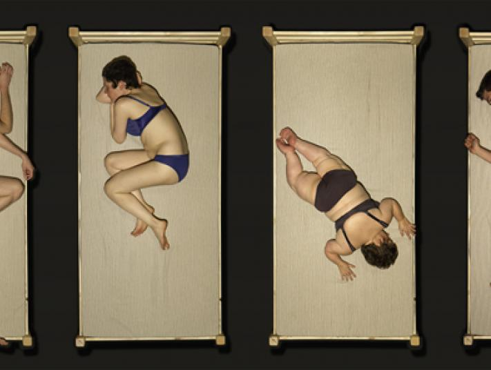 Four people in underwear viewed from above, lie on plain white beds.