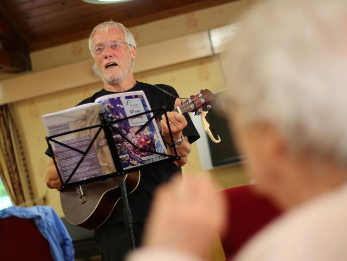 An elderly man plays guitar in front of care home residents.