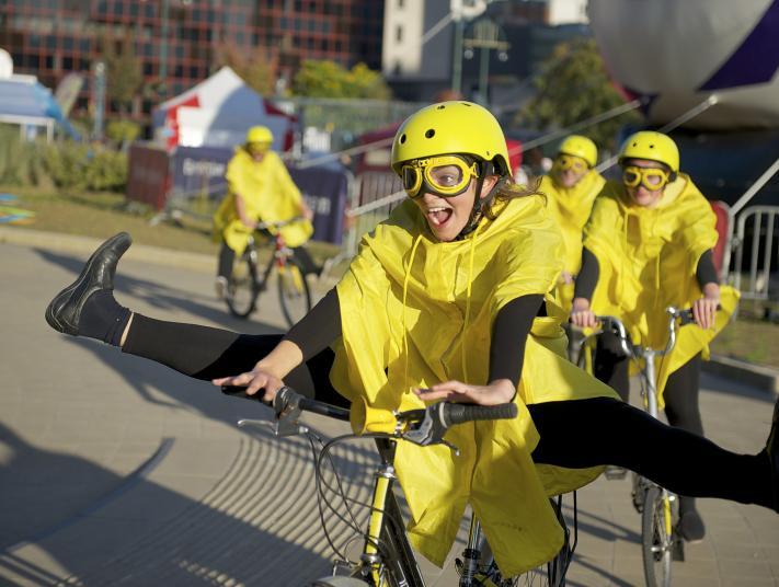 A woman in bright yellow poses with her legs out wide on a bicycle