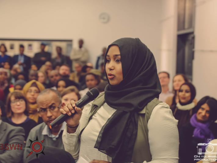 Young Somali woman standing up in room full of people asking a question with a microphone in hand
