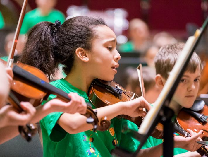 A young girl in a green t-shirt plays the violin with an expression of deep concentration
