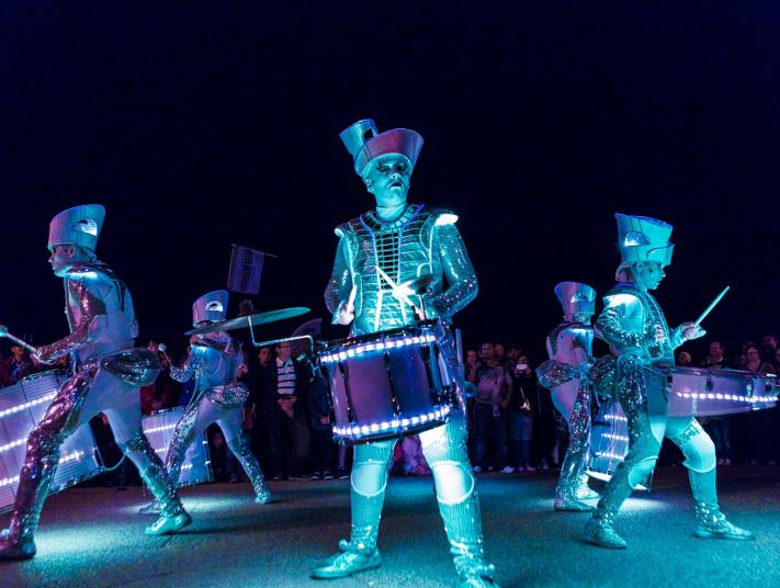 A group of drummers perform in neon costumes during SeaChange arts: Worldbeaters' Spark! Out There Festival, 2016.