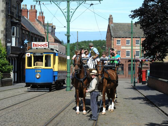 A horse and cart stops beside a tram at Beamish Living Museum.