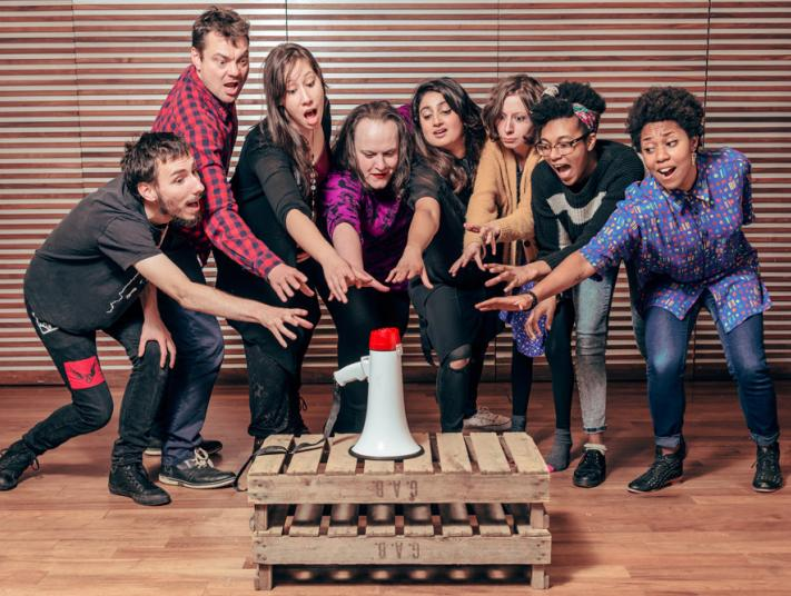Eight performers all reach out towards a megaphone, resting on a wooden pallet in front of them.