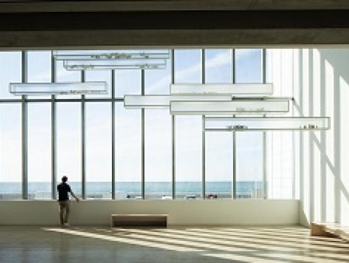 A man at the other end of a large hall looks out through one of several large windows towards the sea.