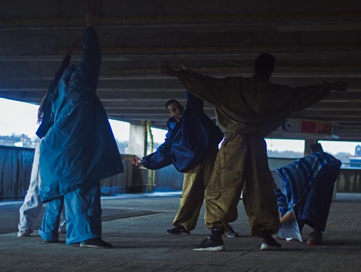 A group of men dance in a multi-storey car park behind the scenes of 'Body Rites' by Naomi Berrio-Allen.