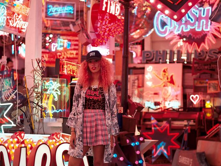 A girl stands amongst a collection of neon street signs as part of confetti crowd film.