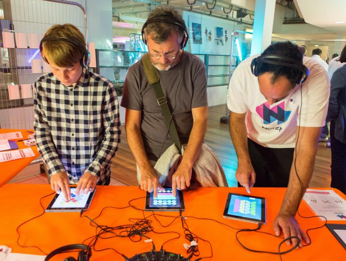 Three men use iPads to play music and games at Digital Utopia.