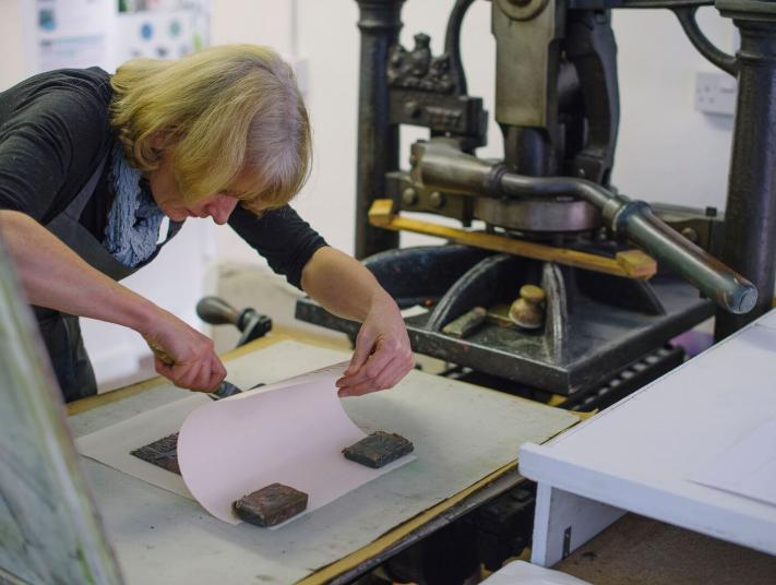 An artist works with a press to create her artwork.