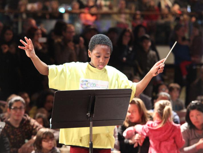 A young boy composes an unseen orchestra in front of an audience.