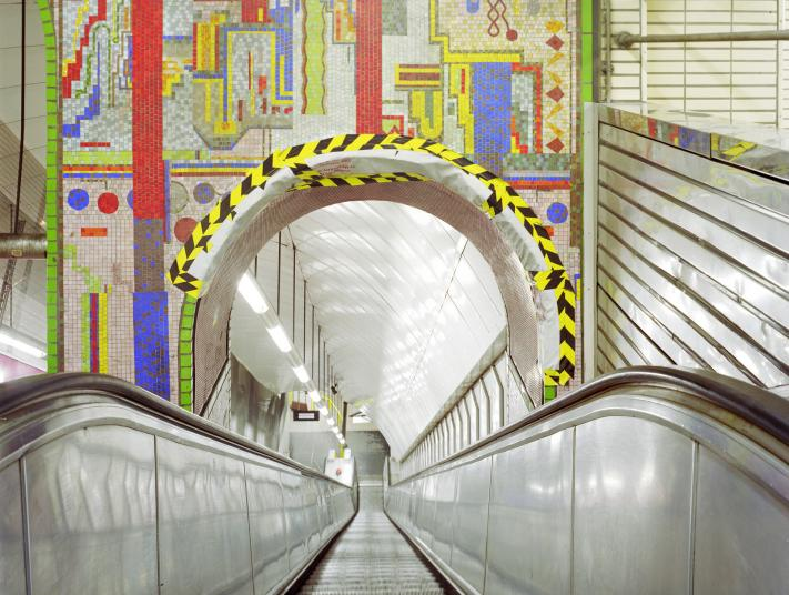 A mural above an escalator in Tottenham Court Road Station, London.