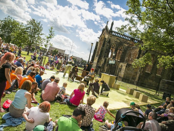 Members of Flex Dance perform in the grounds of a church, watched by a family audience.