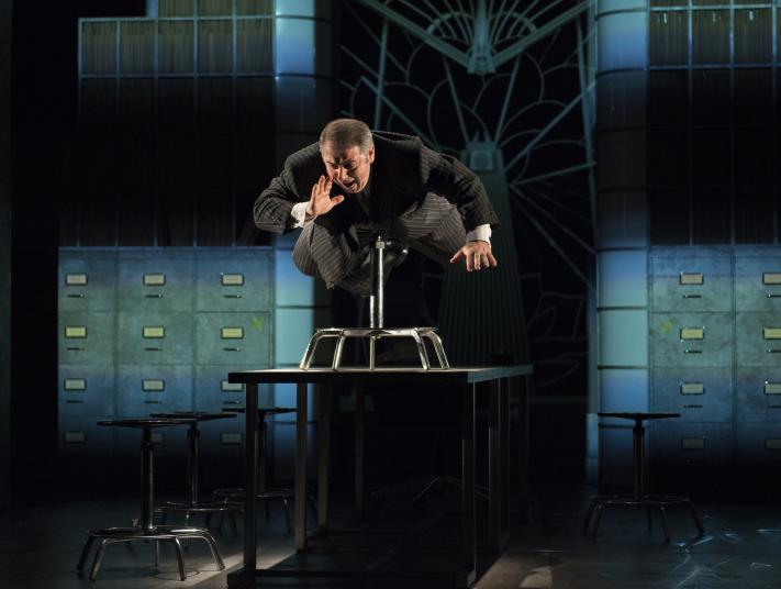 An actor in a pinstripe suit lies across a chair that is stood on a table, surrounded by filing cabinets on stage.
