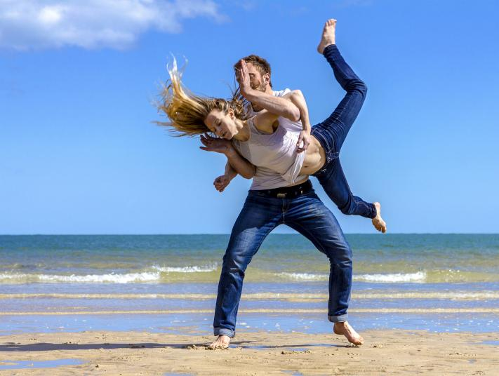 Image of man and woman dancing on beach - man throwing and catching woman with sea in back ground