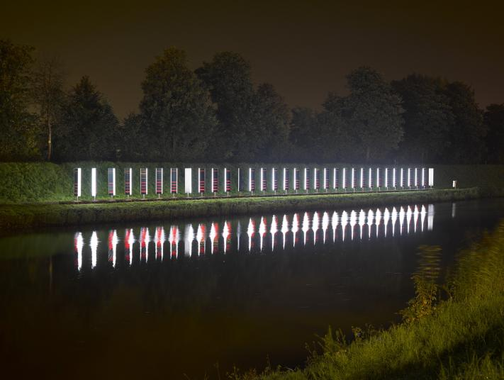 Thirty-three rotating metal lights against a riverbank.