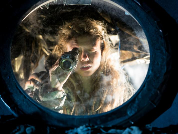 A woman holds a telescope in front of her eye, and stands behind a porthole window.