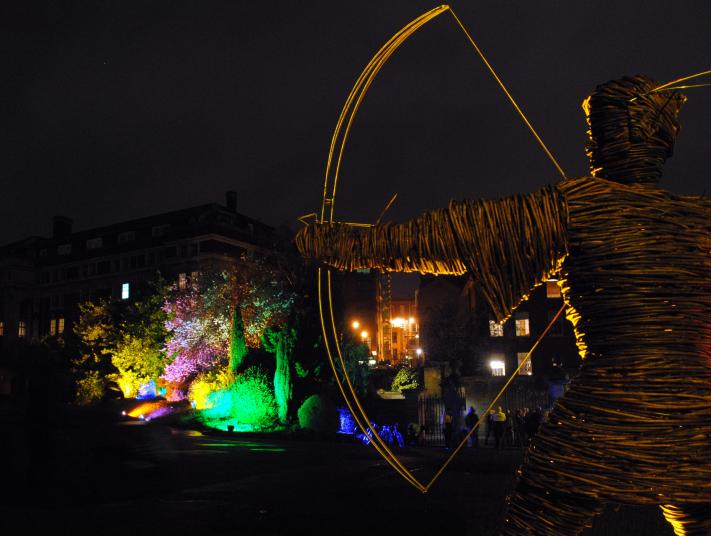 A wicker statue of an archer at night in front of an illuminated castle