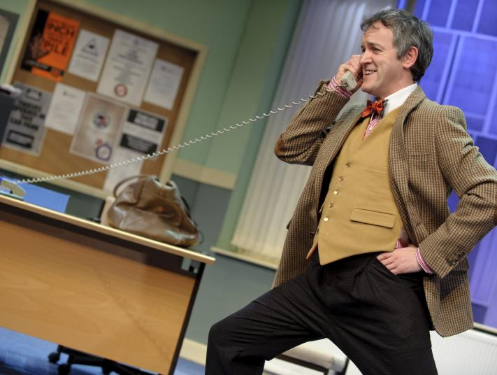 An actor stands in front of a desk on stage, listening to a phone call, with the phone cord stretching from the far side of the desk.