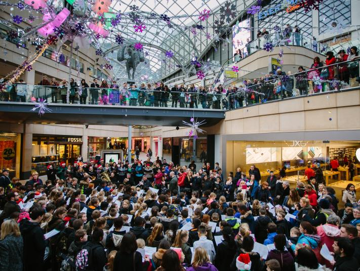 A very large crowd watches a music performance in a Liverpool shopping centre.