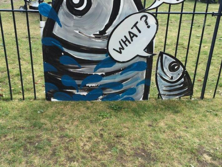 """A cardboard fish is attached to a railing. A speech bubble says """"Out There"""". A small fish's speech bubble is saying """"What!""""."""