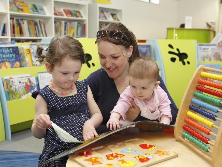 Two young children and a parent read a book in the children's library.