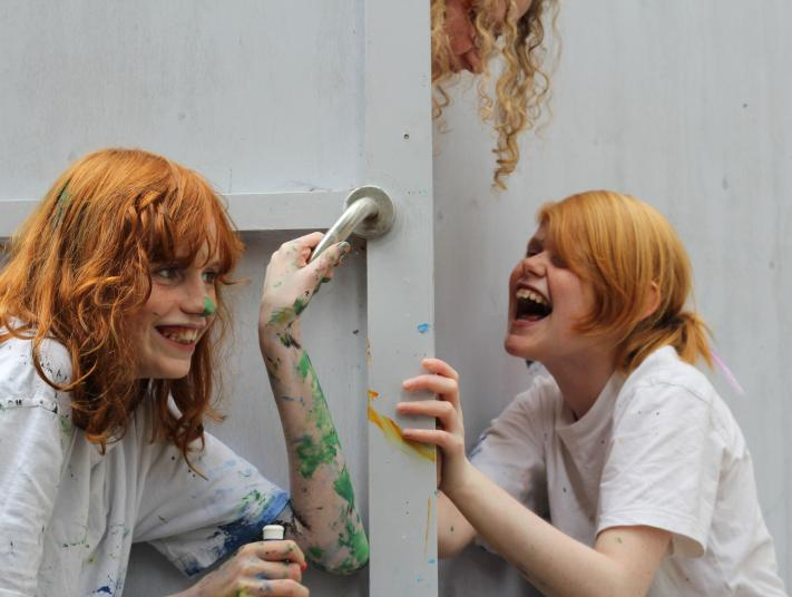 Three young girls with paint on their arms and faces, laugh and play.