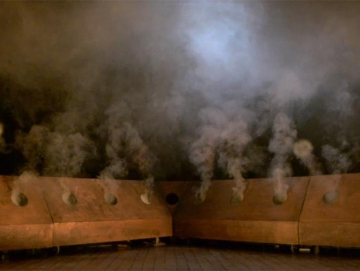 smoke appears from black holes cut into wooden walls.