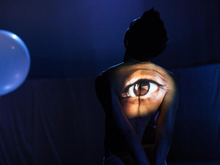 Dancer Subhash Viman stands in sillhouette, with a large eye projected onto his back.