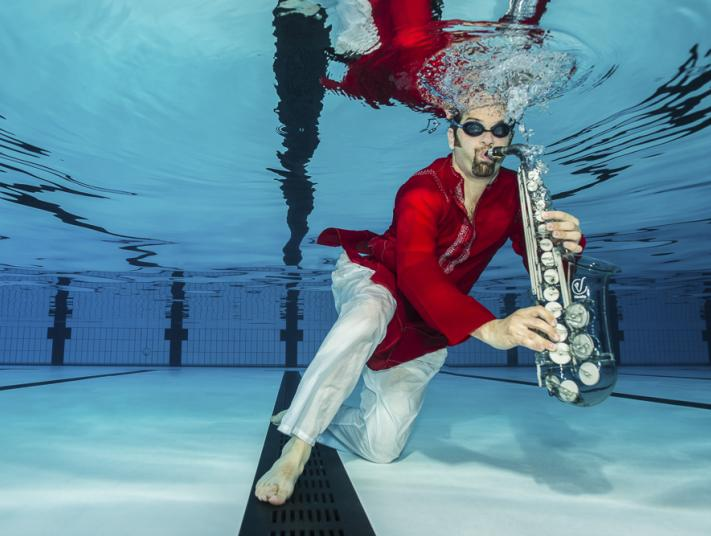 A performer plays a saxophone underwater in a swimming pool.
