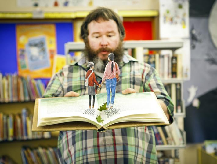 A man holds a pop-up book open in a library.