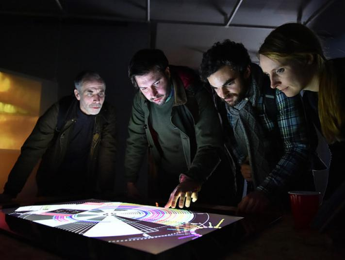 Four people interact with a touch screen.