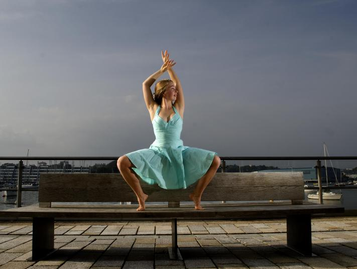 U Dance ballet dancer performs on wooden bench in front of a harbour.