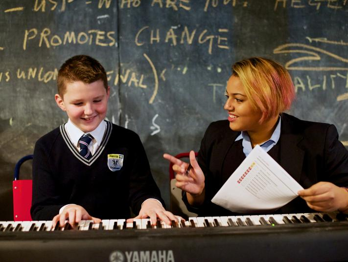 A child in school uniform and a tutor during a keyboard lesson.