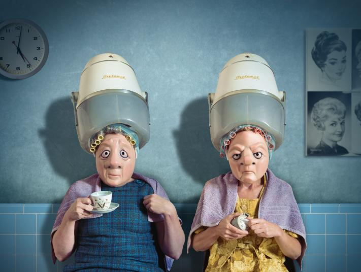 Two performers with 'elderly women' masks sit underneath perming machines on a set resembling a vintage hairdressers.