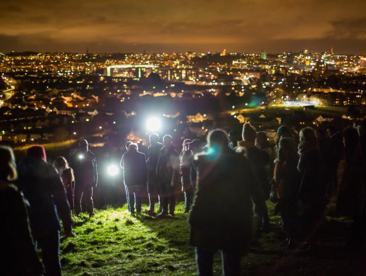 A crowd gathers on a hill at night.