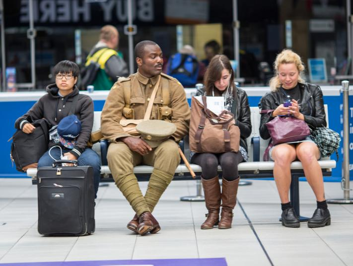 A World War 1 soldier sits next to commuters on a train station bench