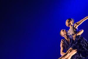 Two black ballet dancers, one male, one female, perform. The man is lifting the  female dancer. She has her arm and leg stretched out.