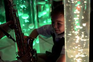 A young girl looks at a saxophone in a sensory room.