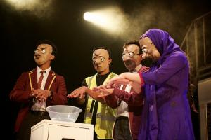 Four performers in papier-mache heads perform on stage.