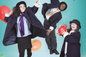 Children dressed in suits jumping with baloons