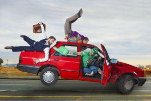 Three men cling on to a red speeding car