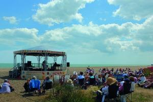 A large group of people sat on the ground or in deck chairs in front of the bandstand on the beach. The sea is in the background and a few clouds sit in the blue sky