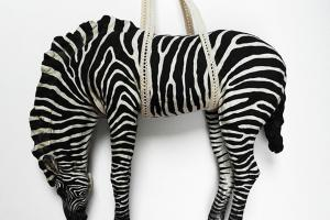 Image of a zebra sculpted from clay hanging in a rope sling